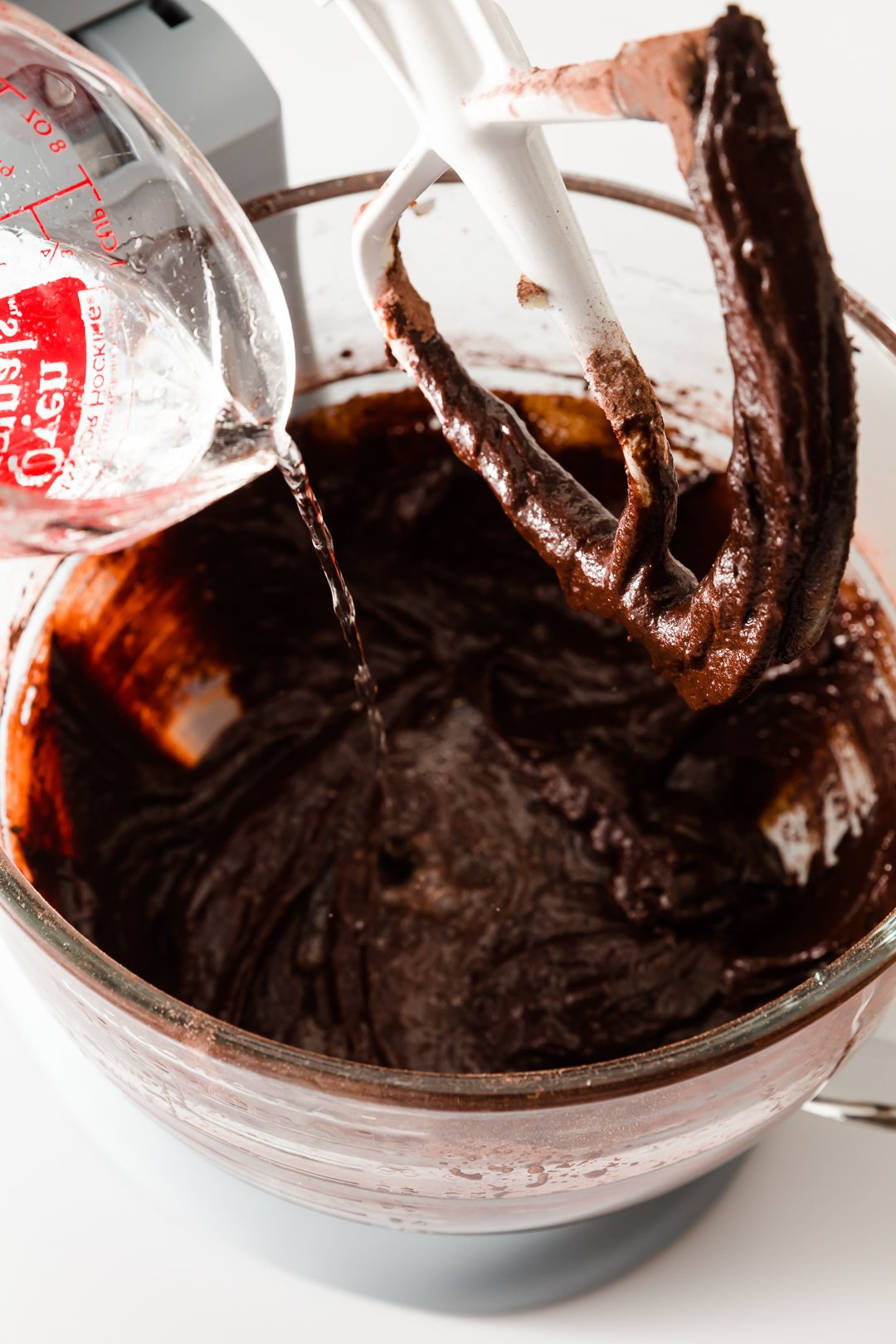 adding water to chocolate cupcake batter