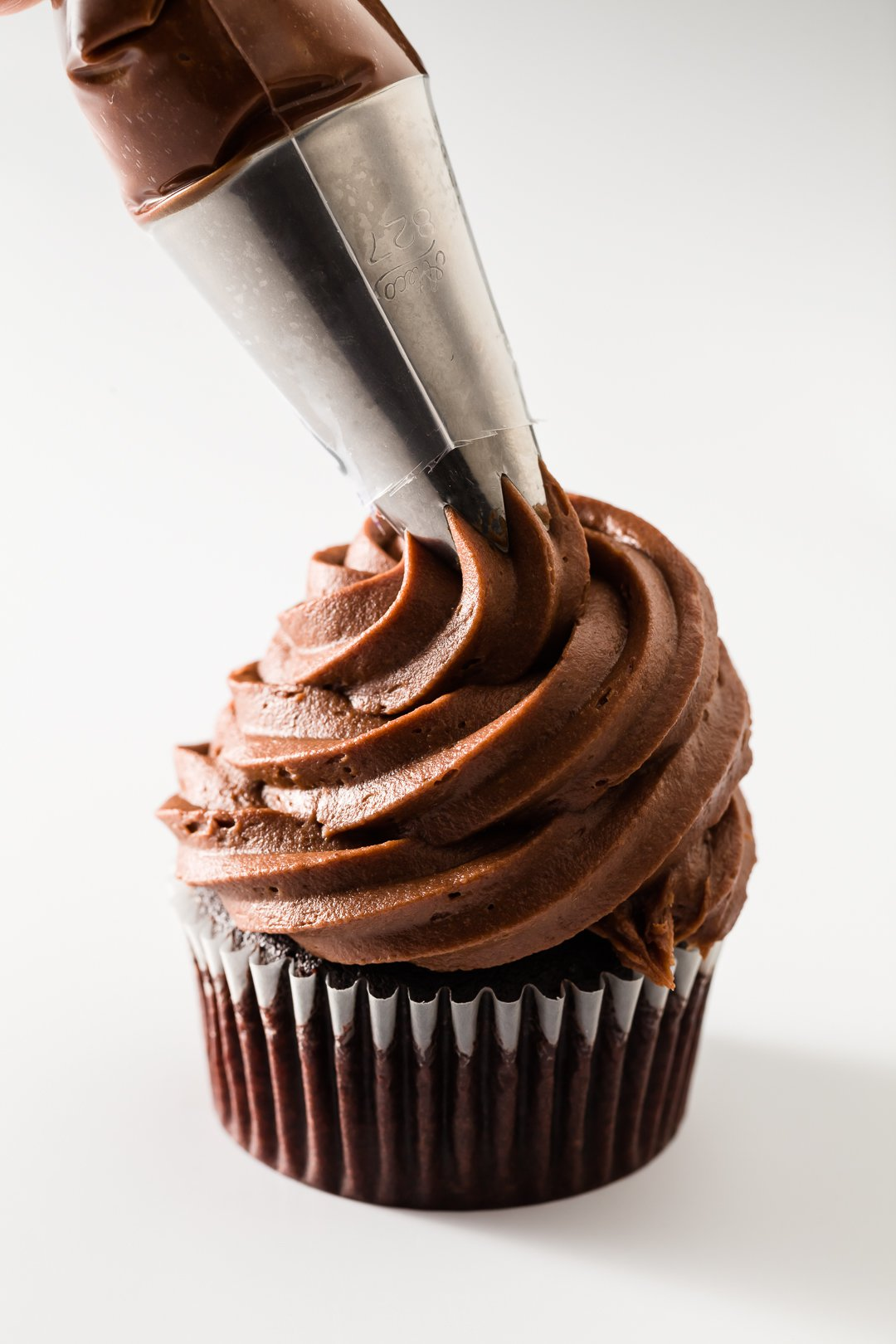 Chocolate cream cheese frosting being piped onto a chocolate cupcake