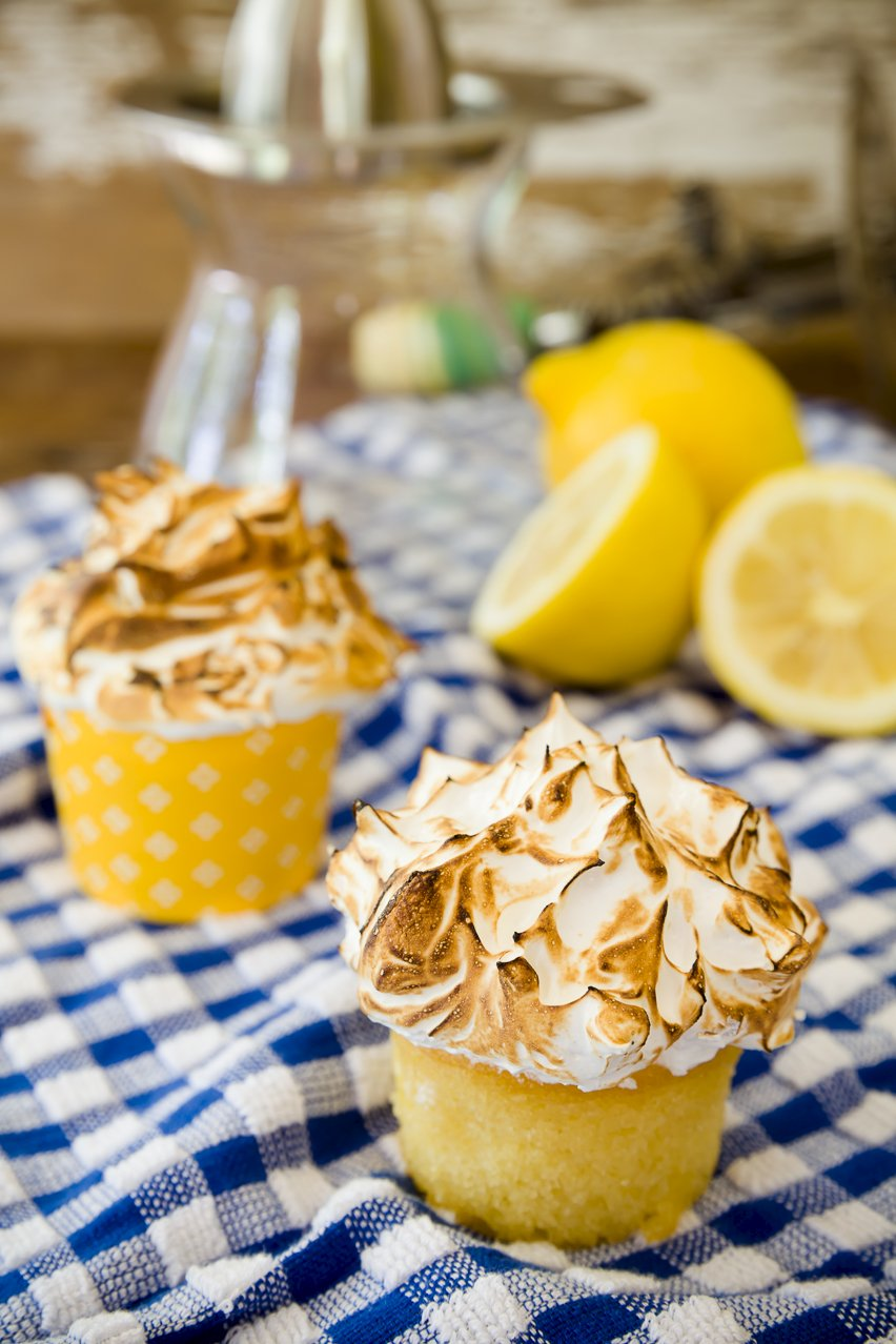 Two mile-high lemon meringue cupcakes with lemons on a checkered tablecloth