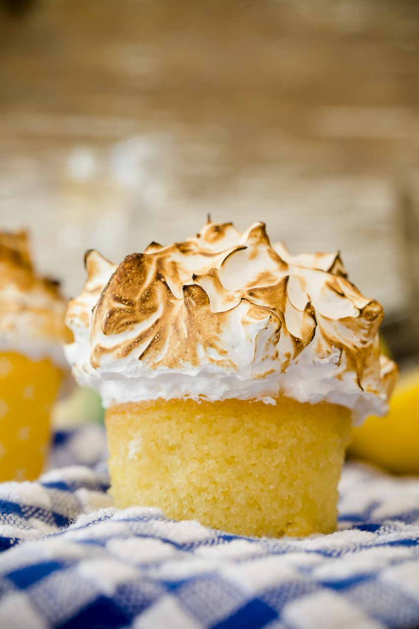Mile-high lemon meringue cupcakes on a checkered tablecloth