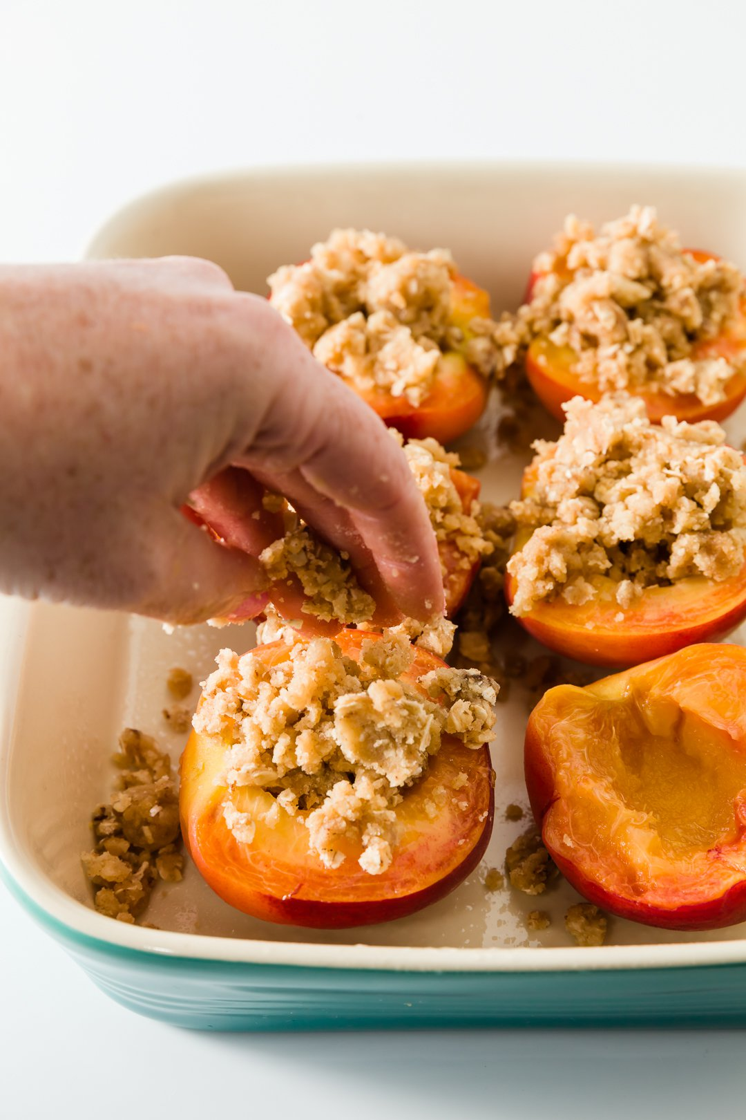 Filling baked peaches with crumb topping