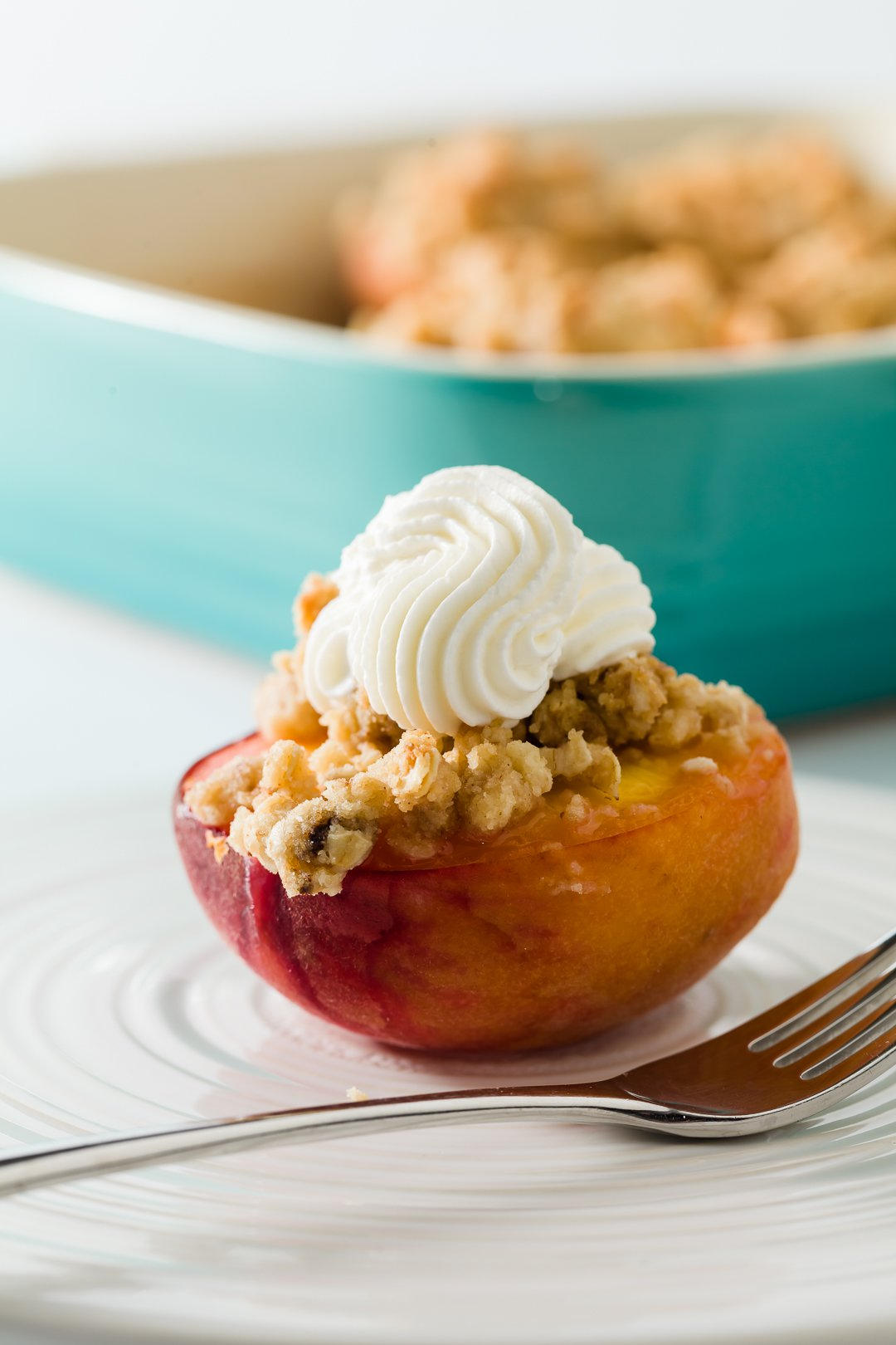 Baked peach with crumb topping and whipped cream