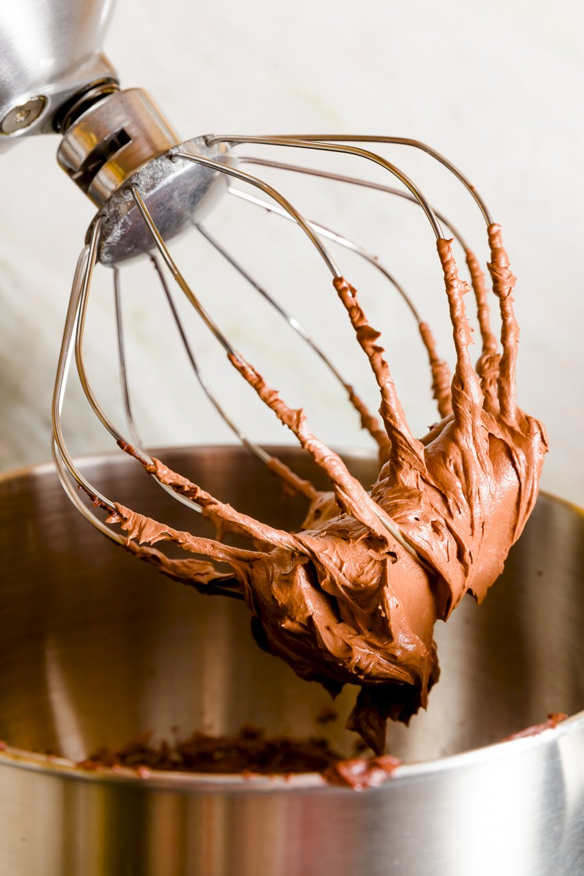 Whipped ganache stuck to a mixer's whisk attachment