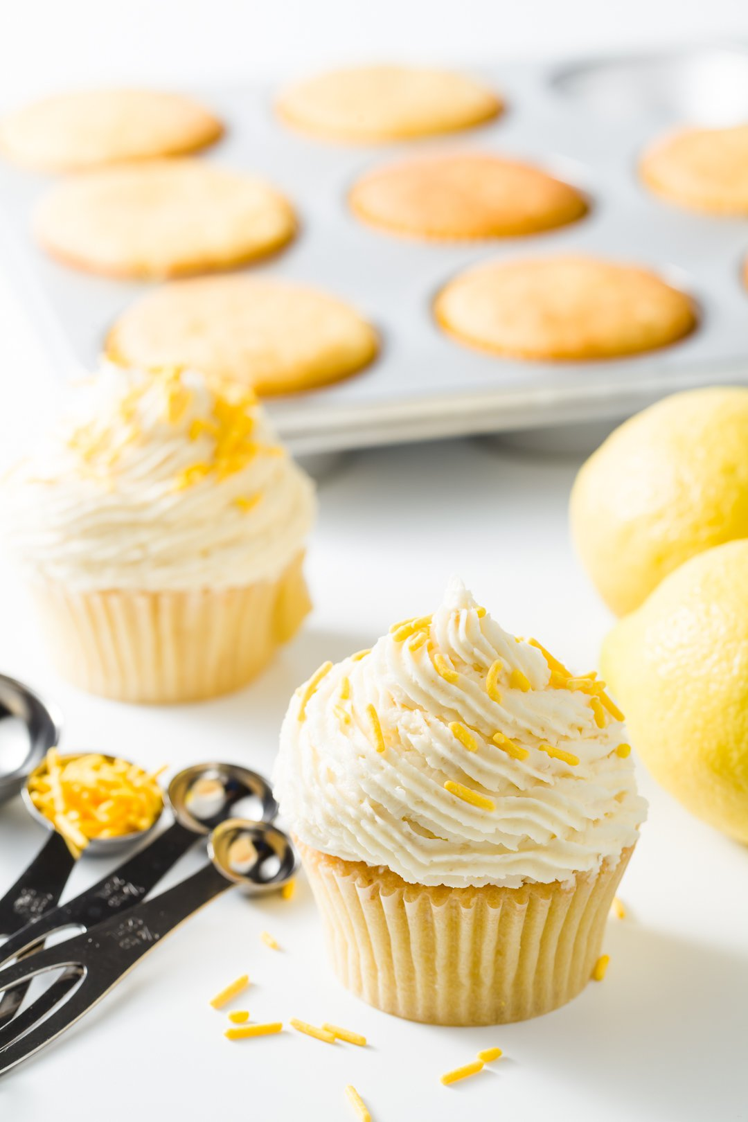 Lemon cupcakes in front of a cupcake tin