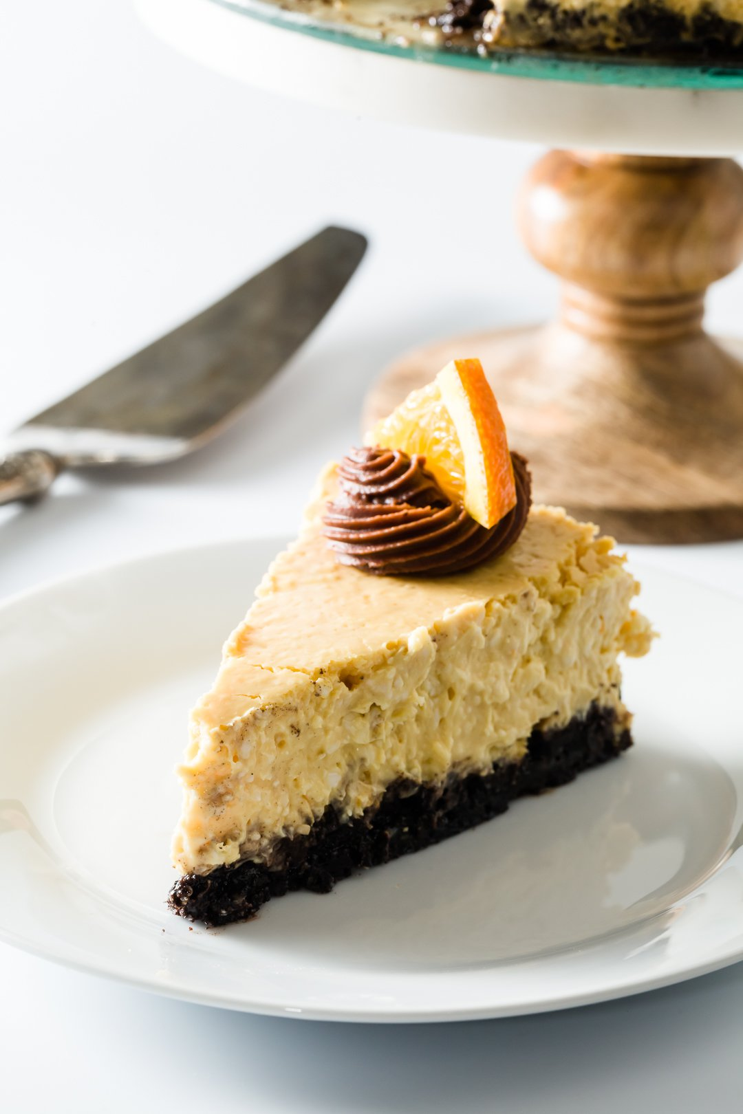 A slice of orange cheesecake with a cake stand in the background