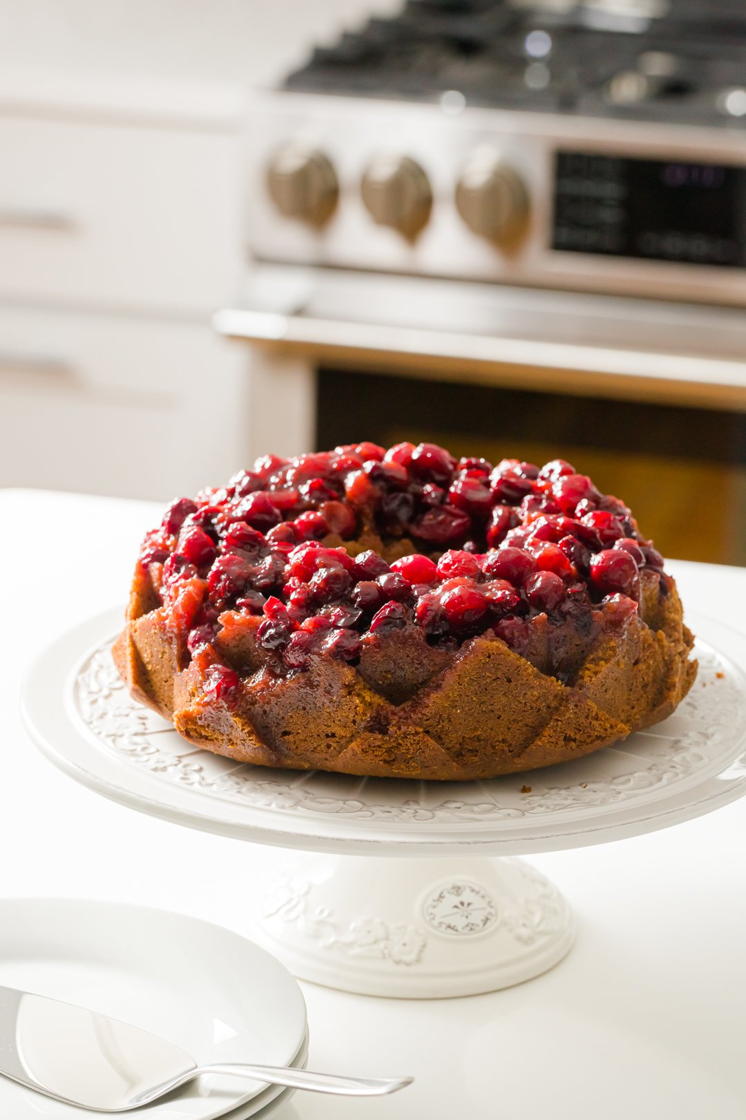 cranberry cake on a cake stand on the counter