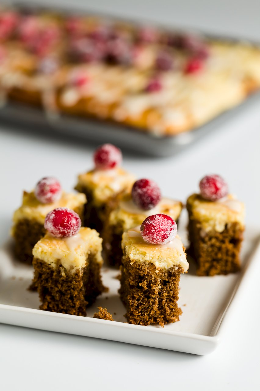 Several small slices of cheesecake-topped gingerbread cake with sugared cranberries