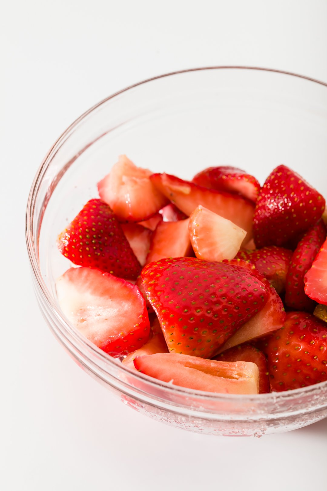 a bowl of glossy macerated strawberries