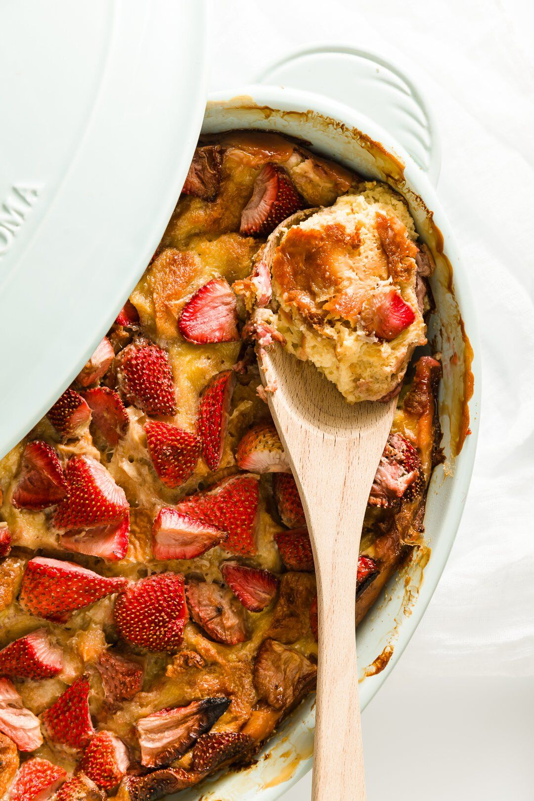 brioche French toast in a casserole dish with some scooped onto a serving spoon