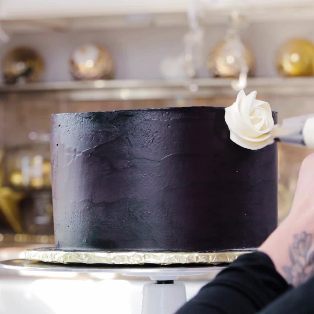 Piping a white rosette onto a black cake