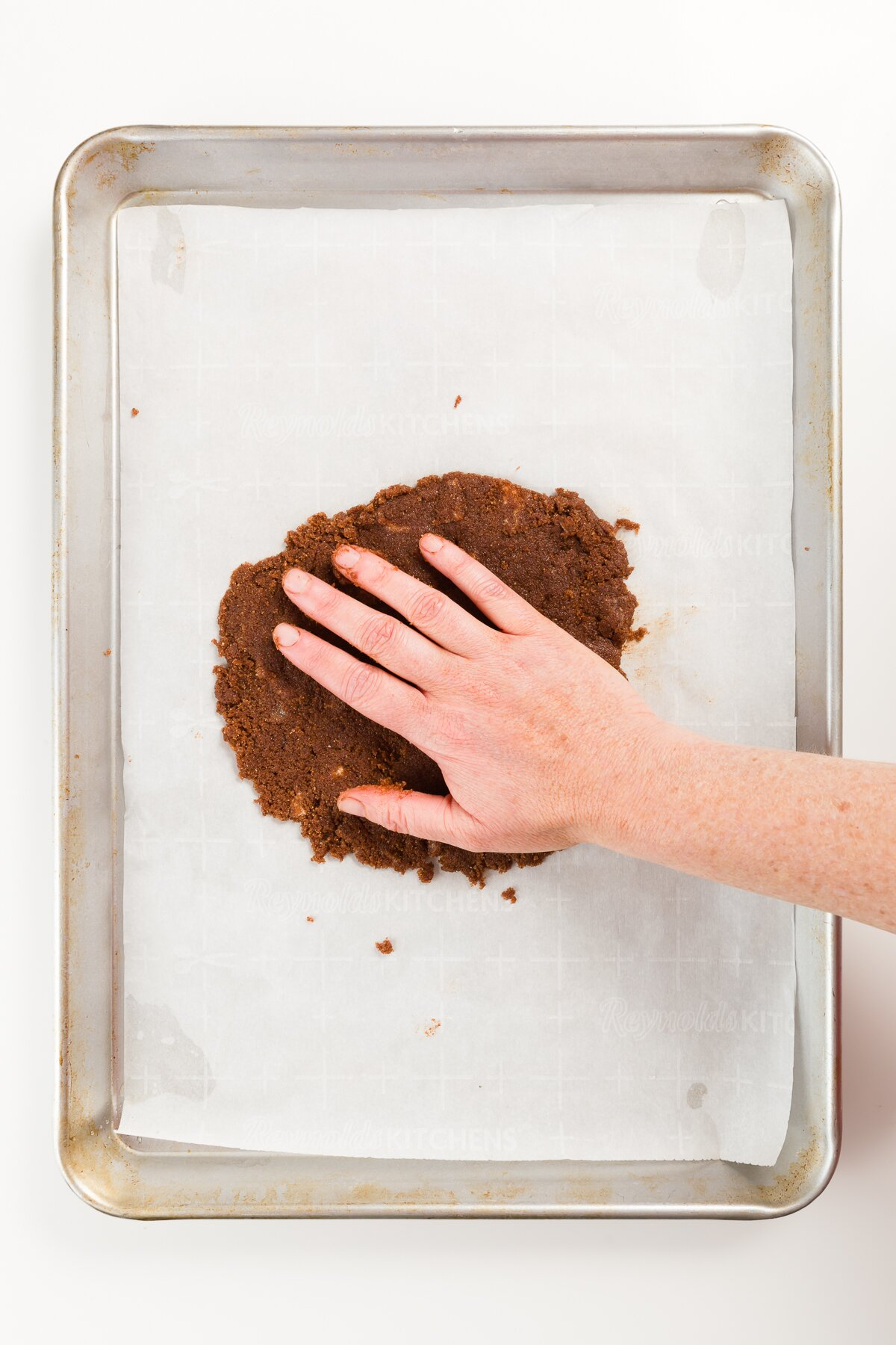Pressing brown sandy mixture onto parchment paper on a cookie sheet