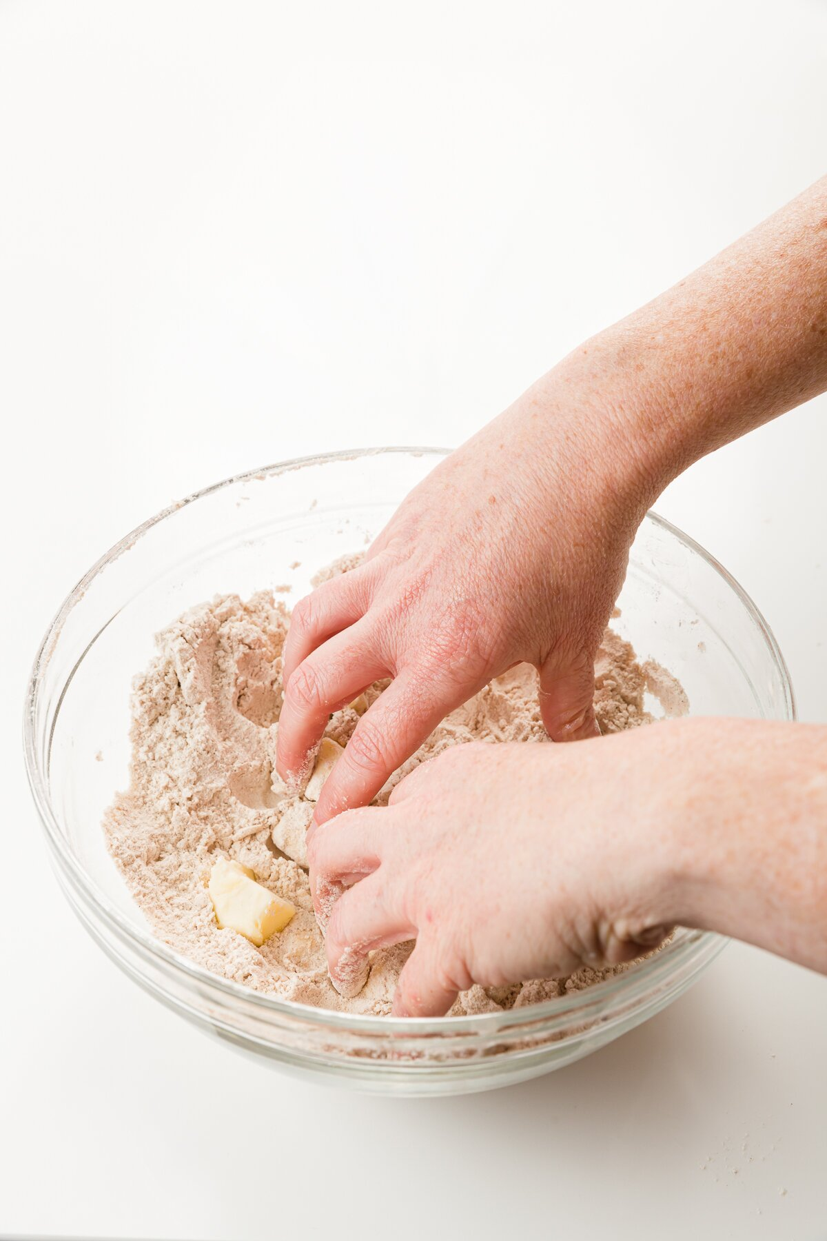 Hands in a glass bowl mixing butter into dry ingredients