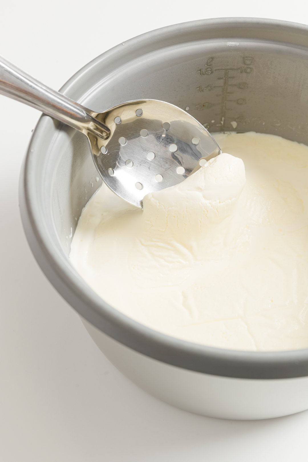 A slotted spoon skimming the clotted cream off of the top of a cream-filled rice cooker bowl