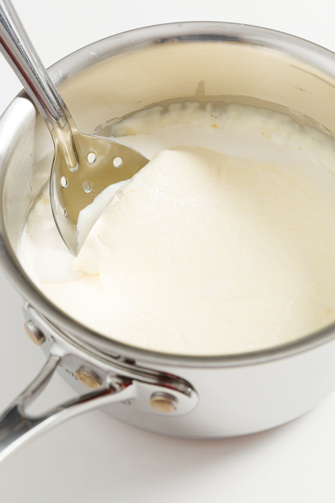 Skimming clotted cream in a pot using a slotted spoon