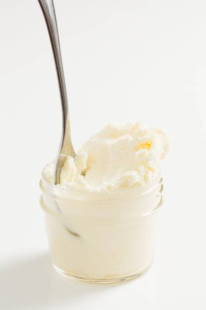 A jar of clotted cream with a spoon resting inside