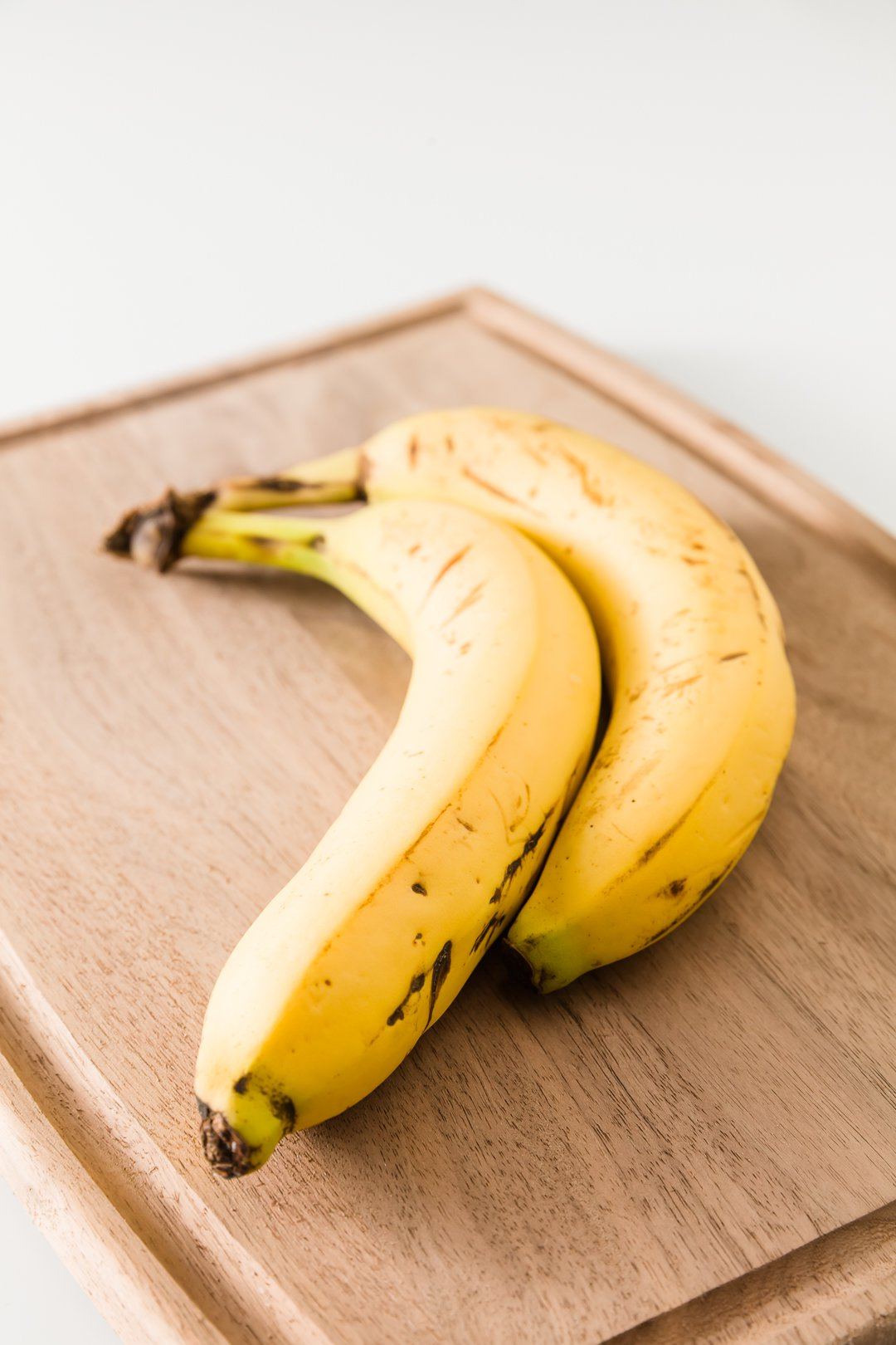 Two yellow bananas with just a few brown spots on a cutting board