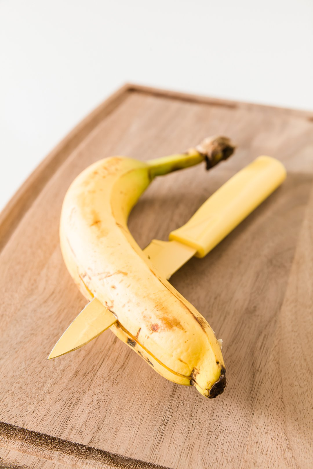 A knife slicing a banana