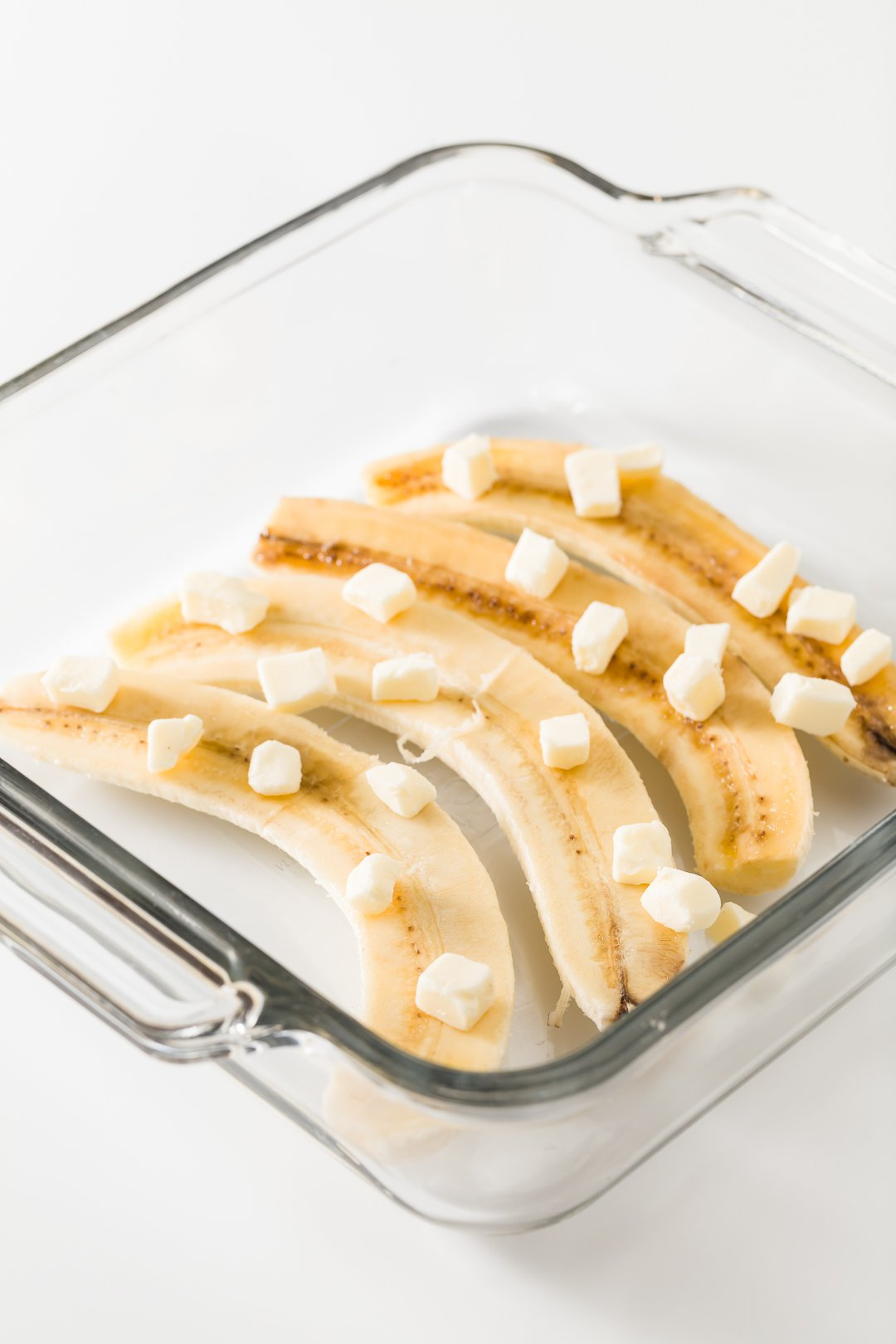 bananas in a glass dish topped with butter