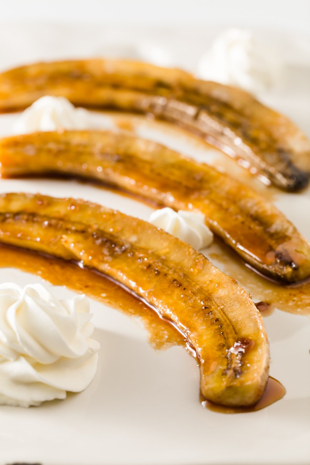 caramelized banana halves on a plate with whipped cream