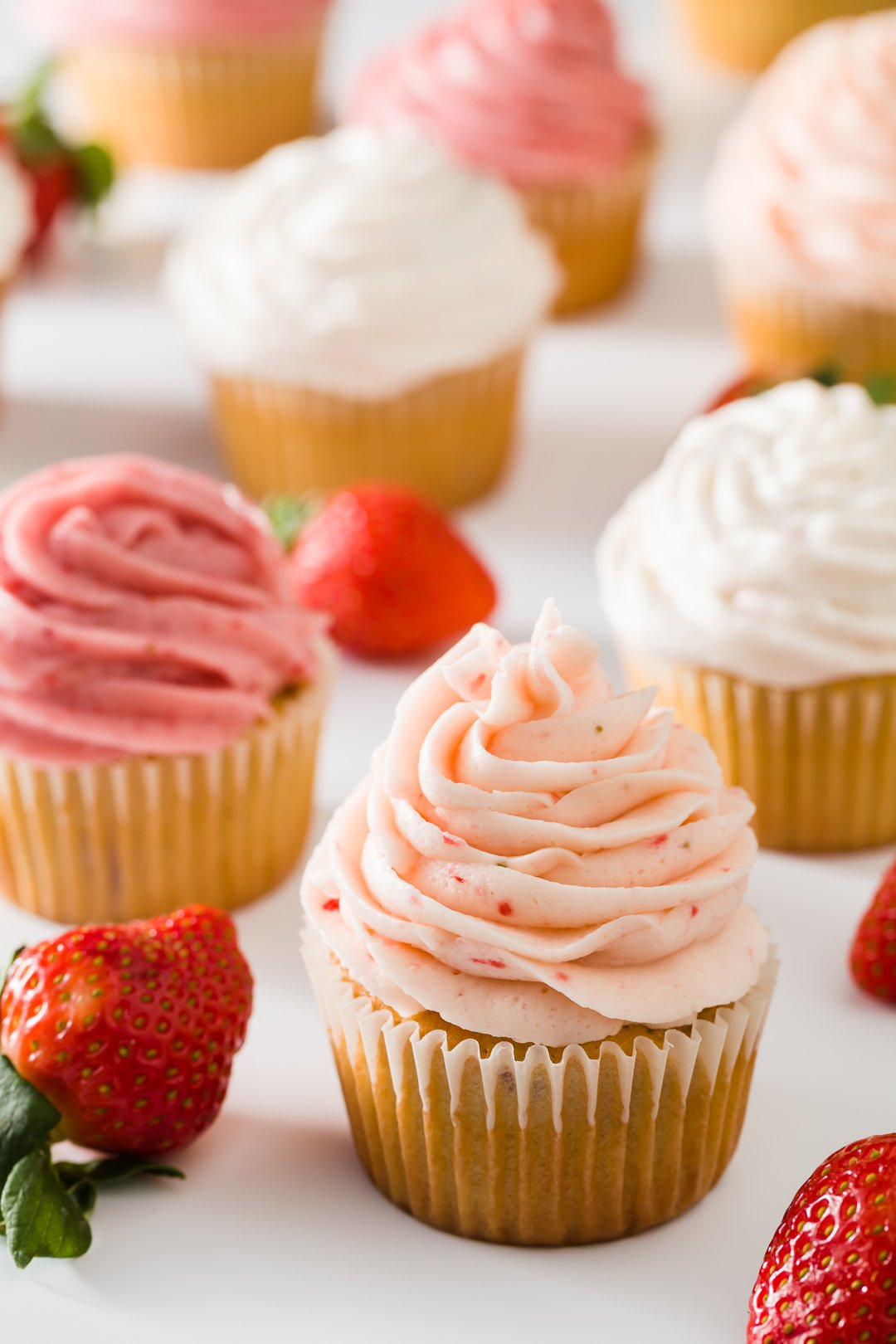 cupcakes frosted with three types of strawberry frosting on a white background with some scattered strawberries