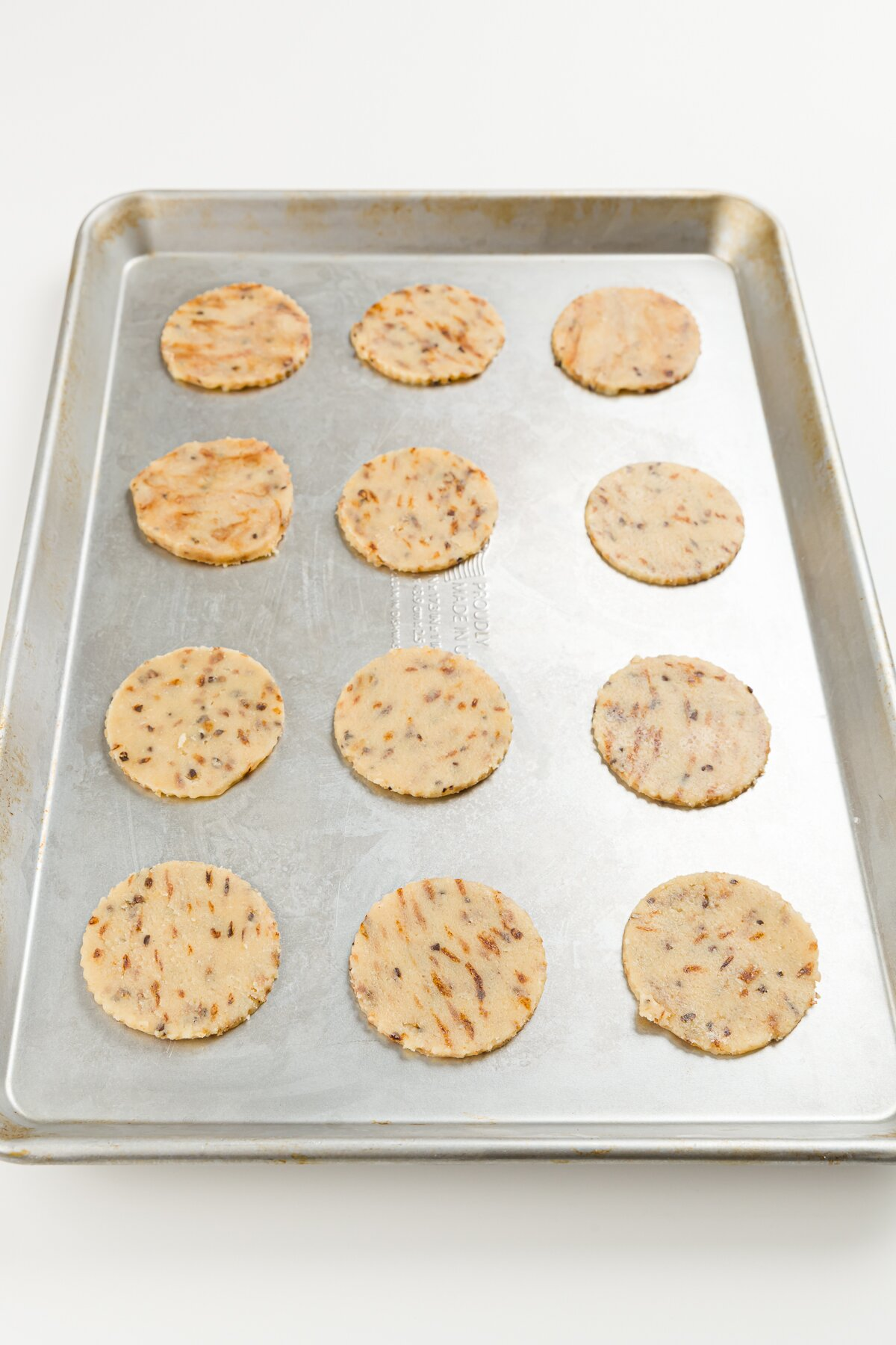 16 coffee cookies on a cookie sheet ready to go in the oven
