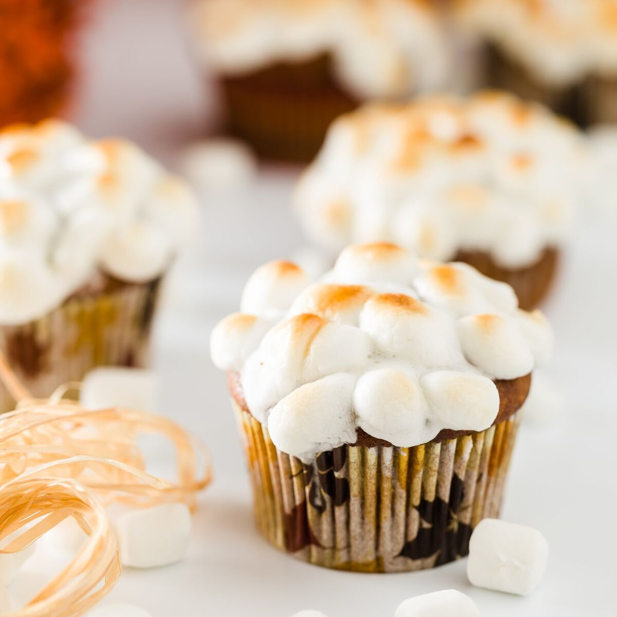 a group of sweet potato cupcakes topped with mini marshmallows