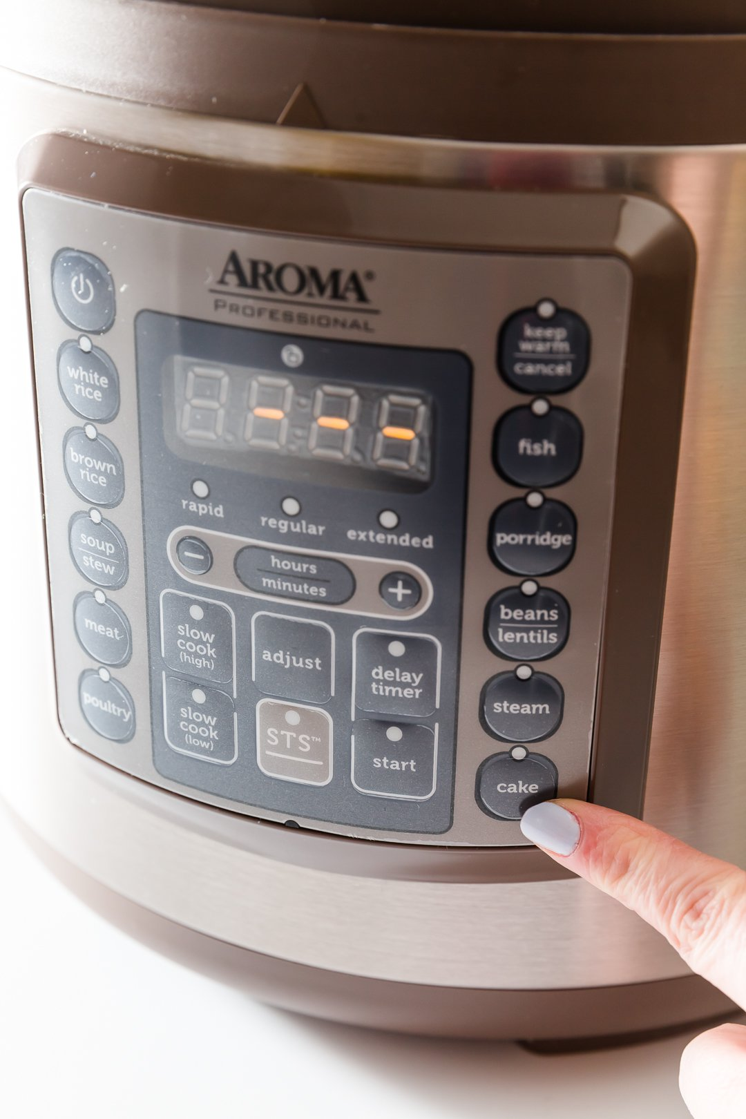 Pointing at the cake button on Aroma's pressure cooker
