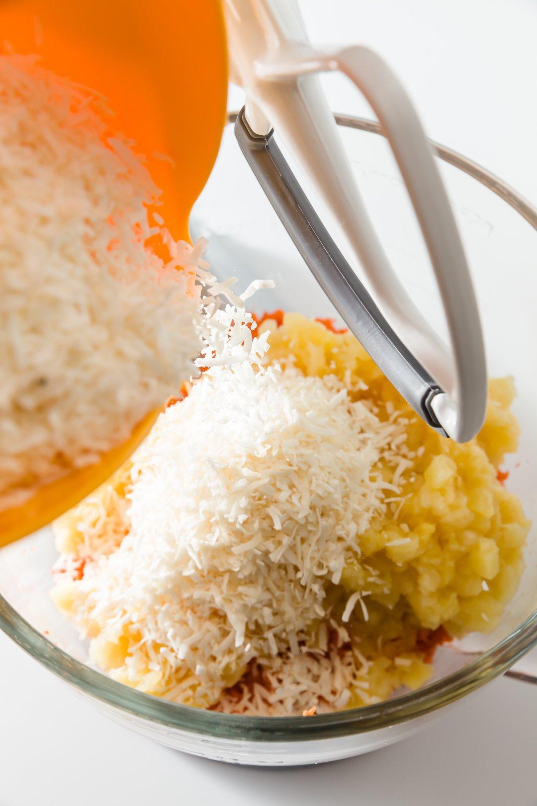 Se agrega coco rallado a la masa de pastel de zanahoria