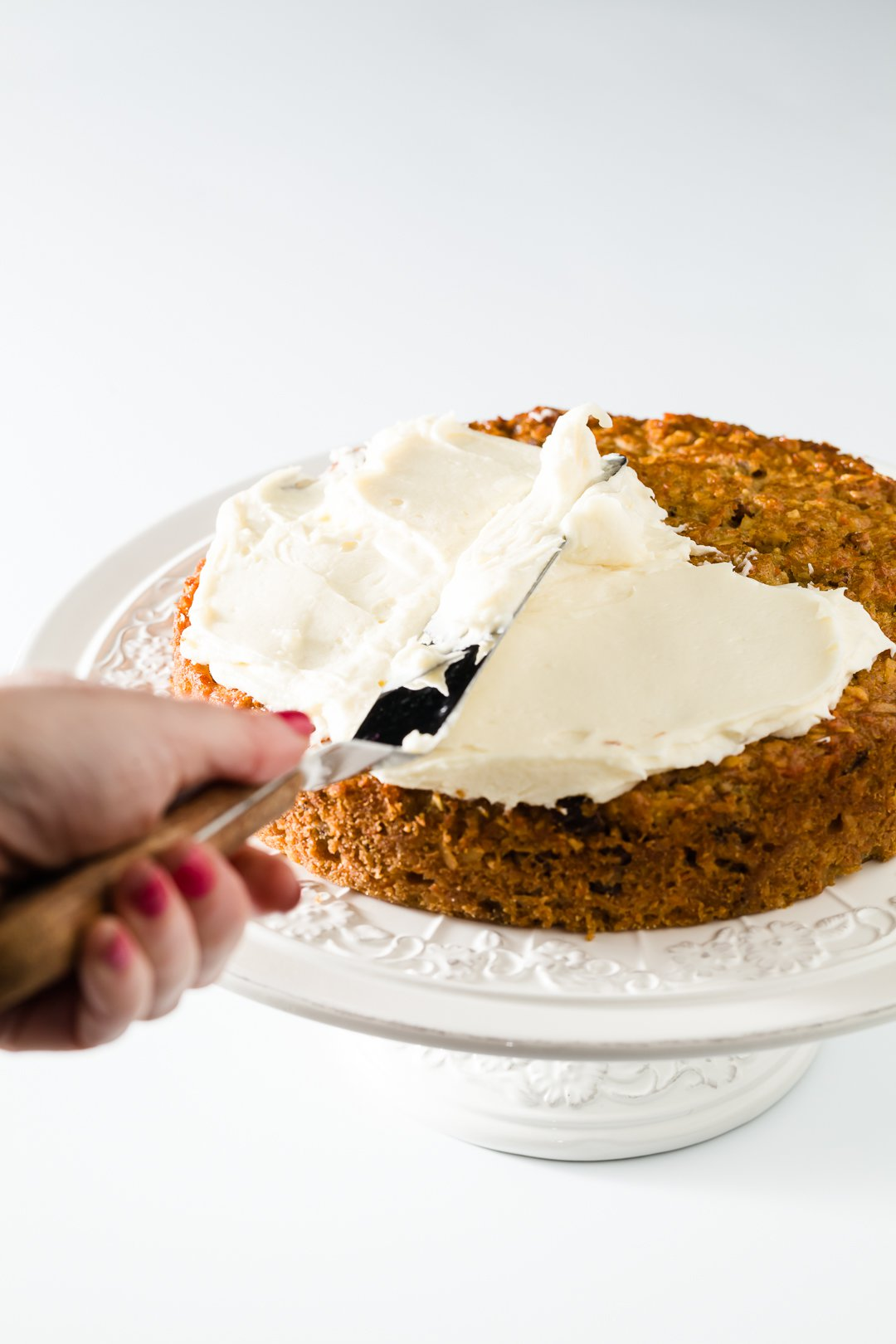 Spreading cream cheese frosting on a carrot cake