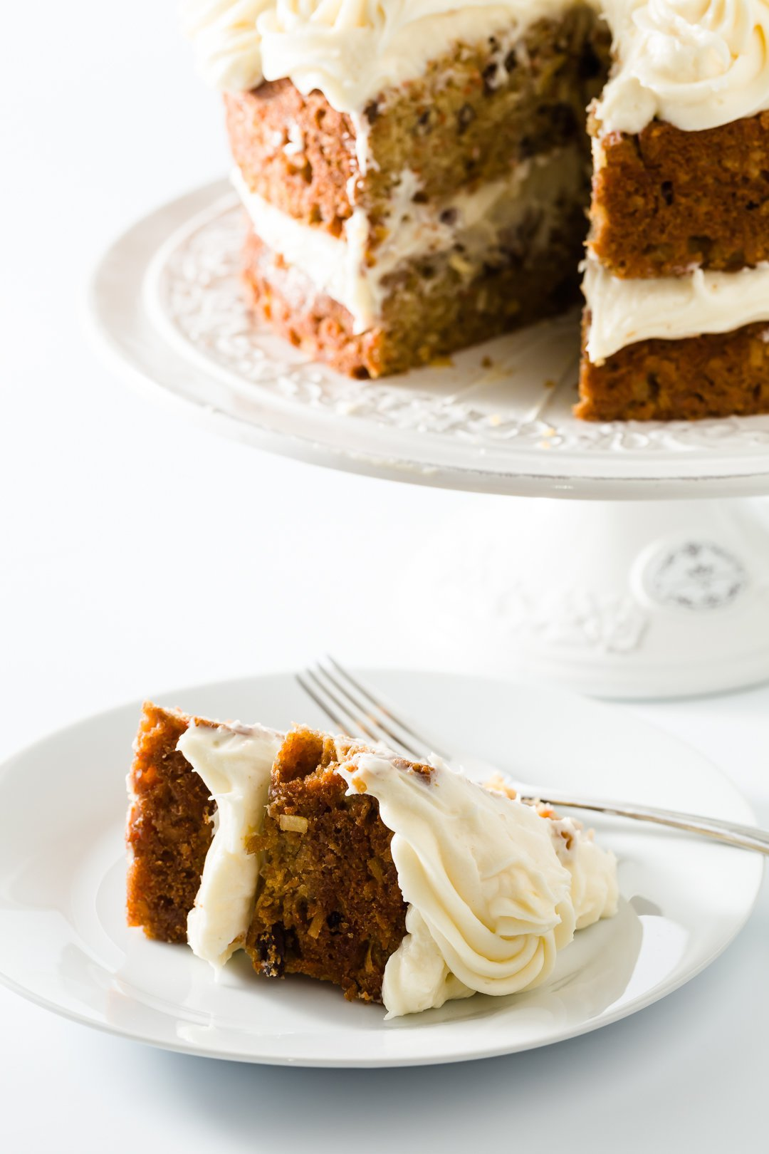 Slice of carrot cake in front of the whole cake