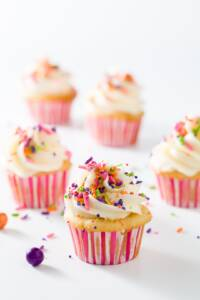 A group of mini cupcakes in pink and white liners