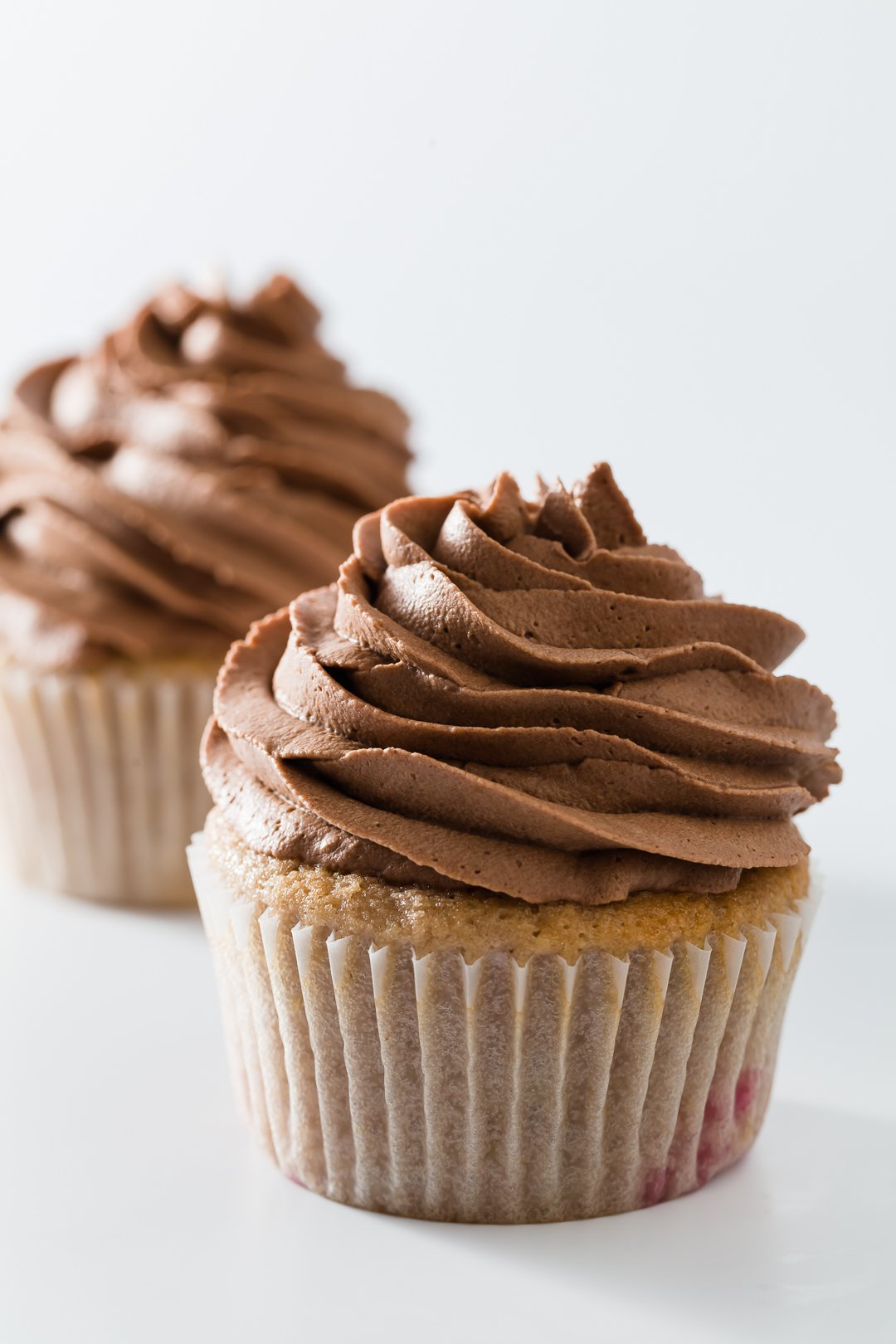 Two cupcakes topped with chocolate whipped cream