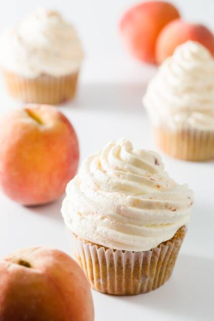 Cupcakes topped with peach whipped cream