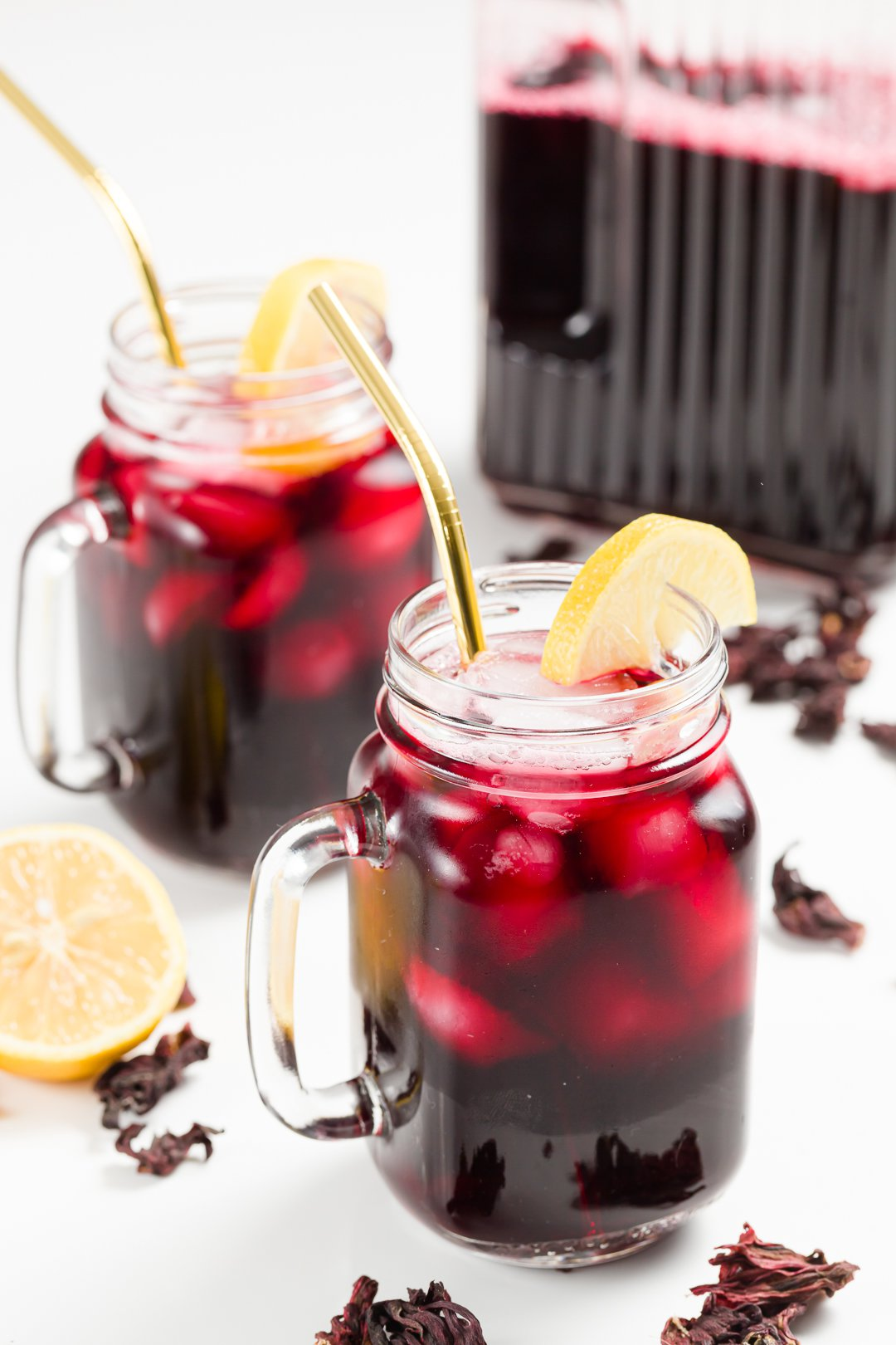 Two glasses of iced hibiscus tea garnished with lemon