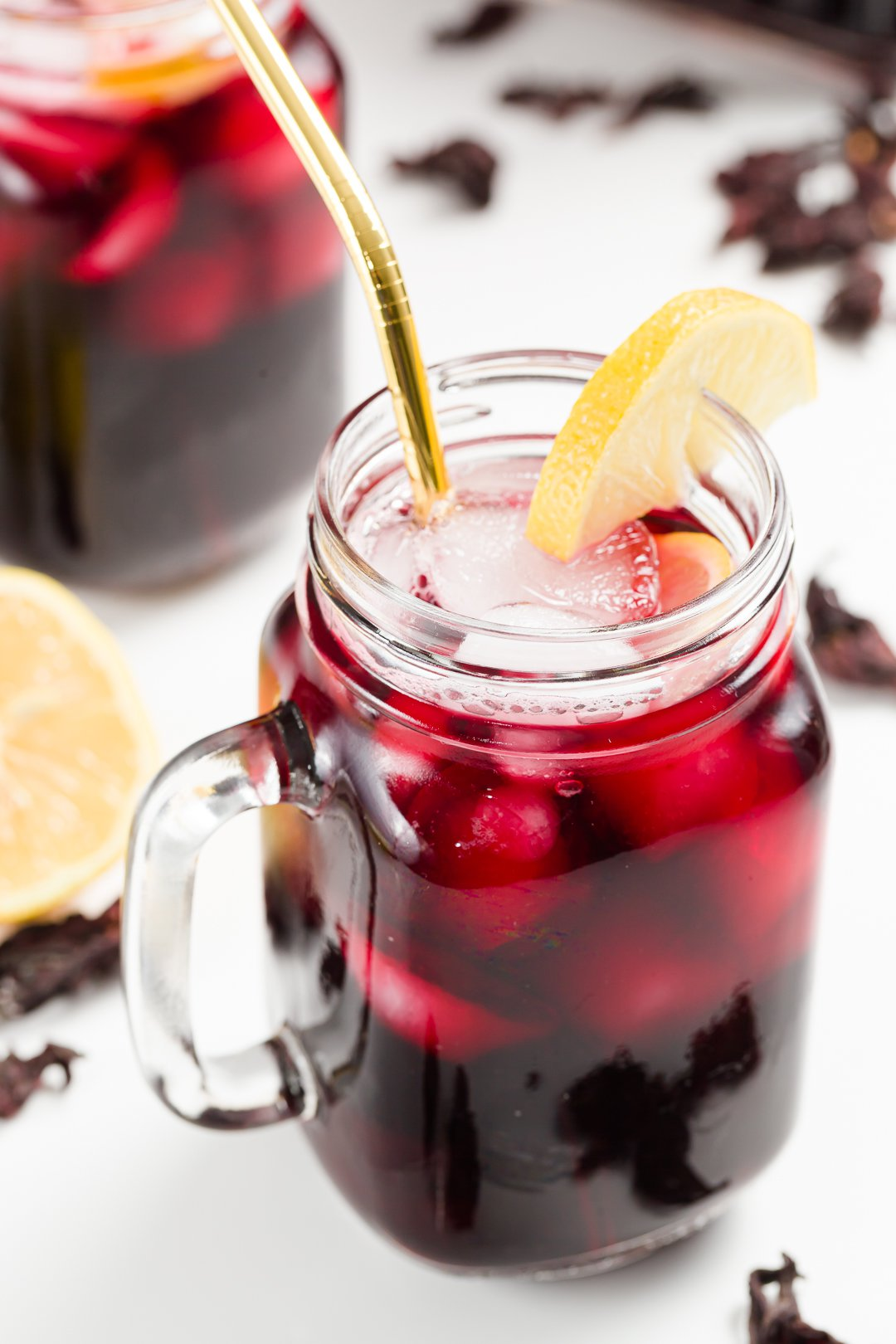 A glass of iced hibiscus tea garnished with lemon