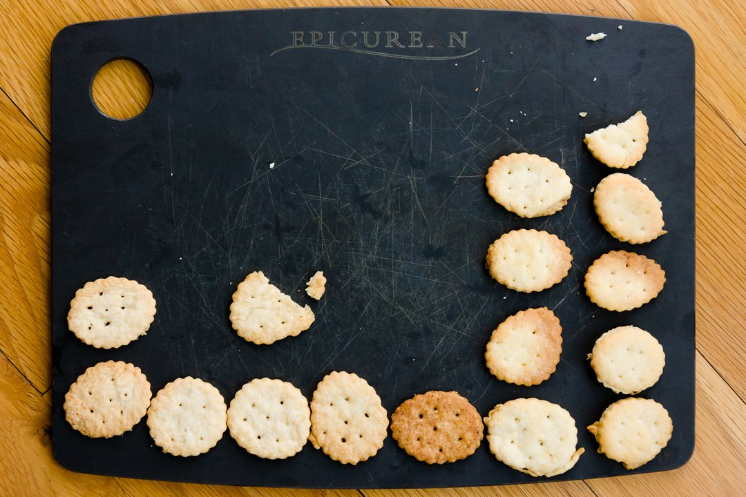 Columns of homemade Ritz cracker experiments on a cutting board
