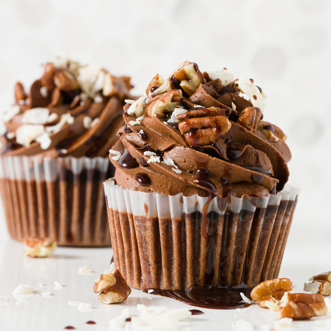 Two German chocolate cupcakes on a counter decorated with chocolate frosting swirls, coconut flakes, pecans, and drizzled with chocolate syrup