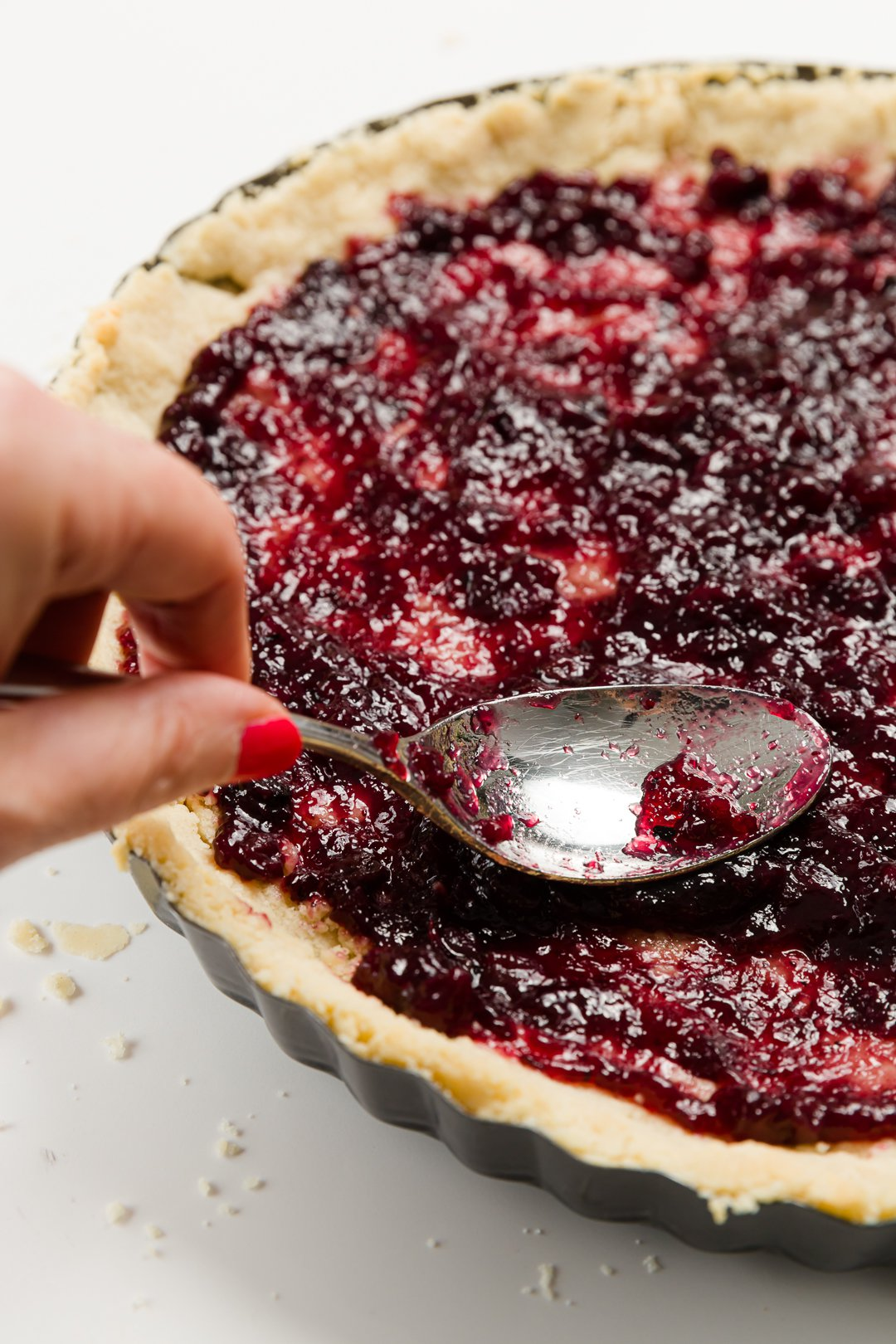 Spreading jam on an unbaked tart using the back of a spoon