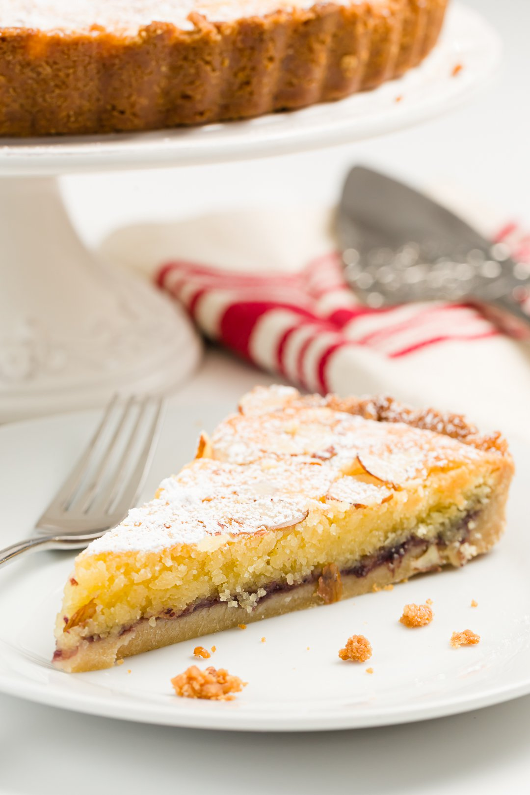 Slice of bakewell tart on a plate with a fork and the whole tart on a stand in the background