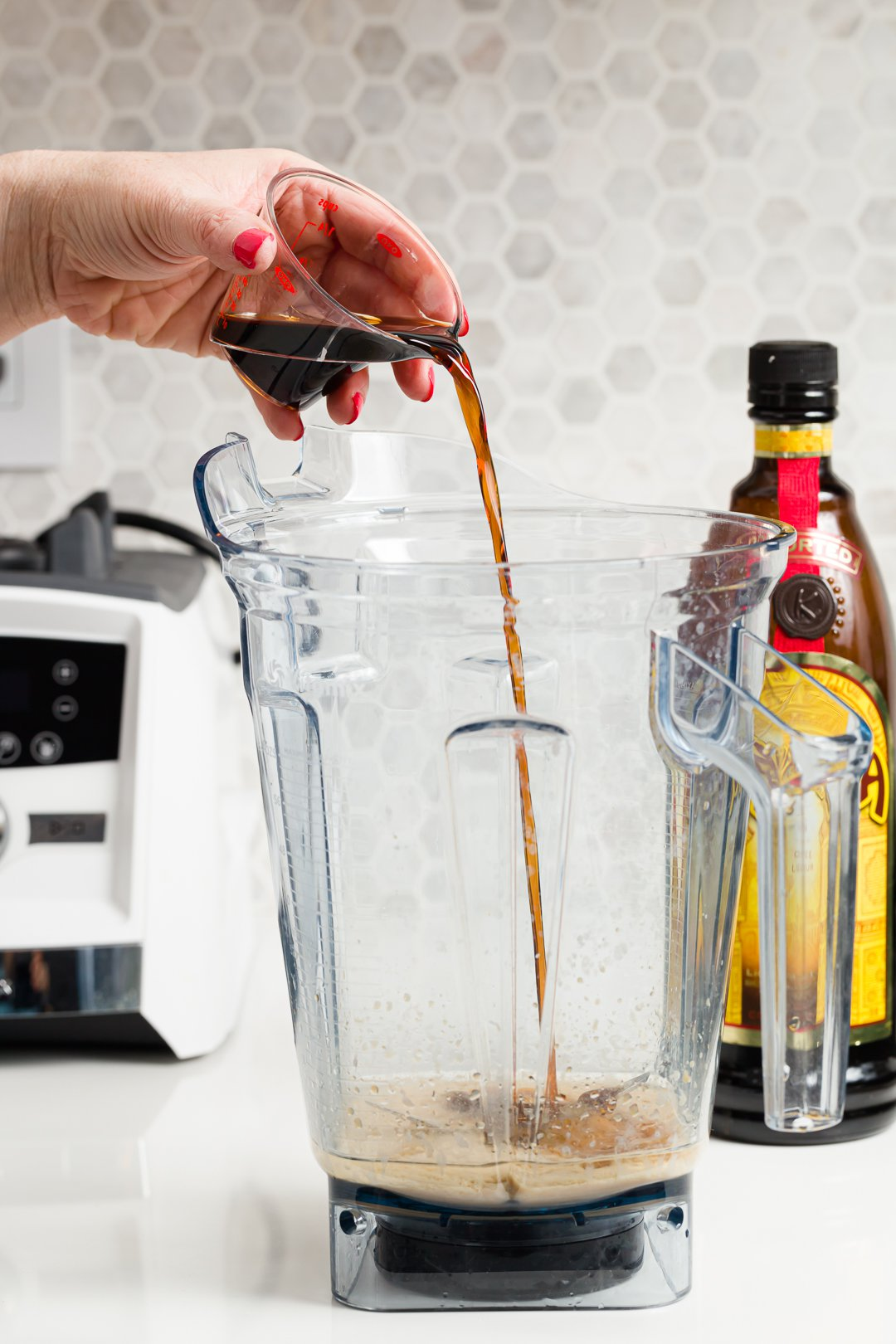 Stef pouring Kahlua into a blender to make a frozen mudslide cocktail