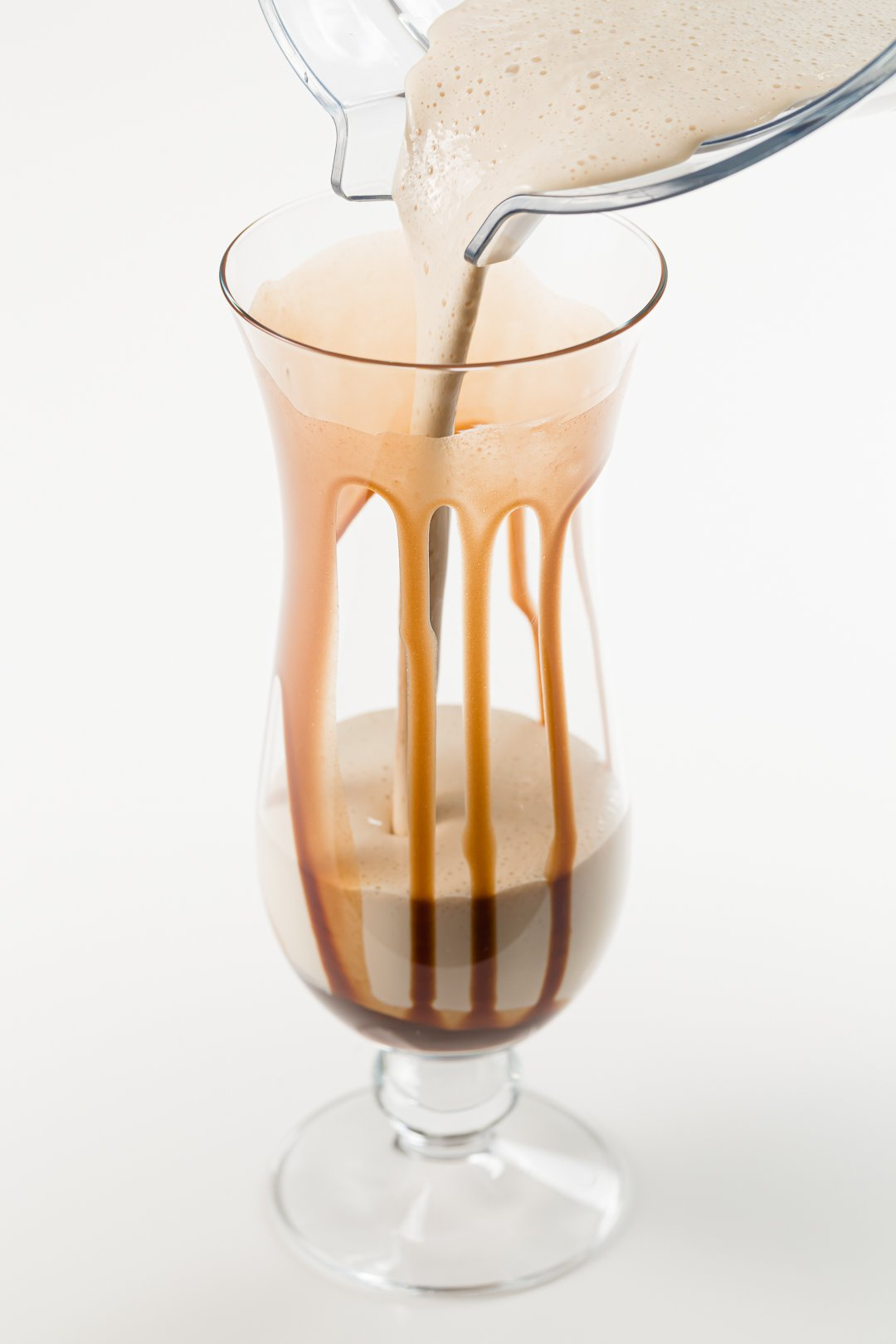 pouring from a pitcher of frozen mudslide cocktails into a glass drizzled with chocolate sauce
