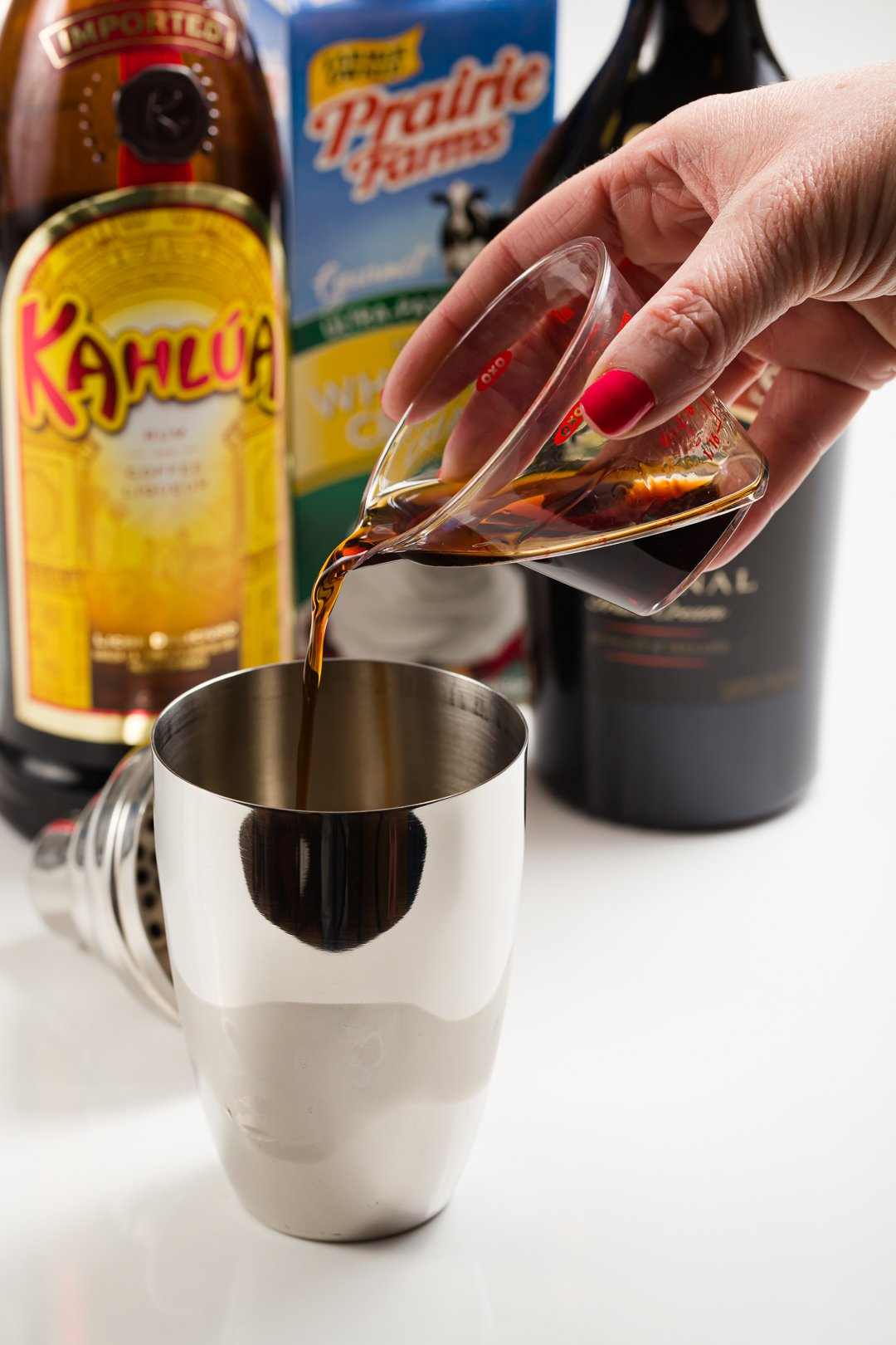Kahlua added to a cocktail shaker with ice to make a mudslide cocktail