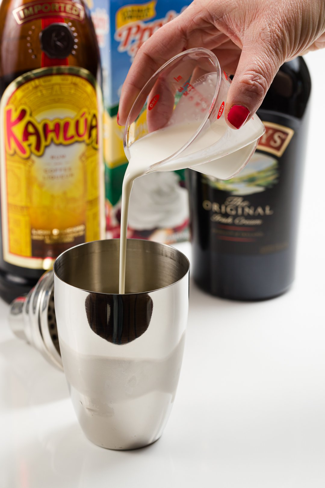 heavy cream added to a cocktail shaker with ice to make a mudslide cocktail