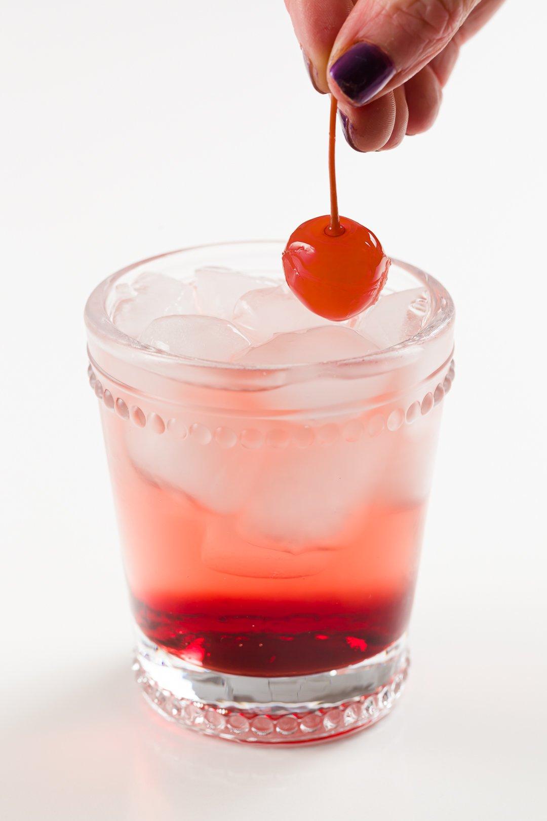 placing a Maraschino cherry into a Shirley Temple non-alcoholic cocktail