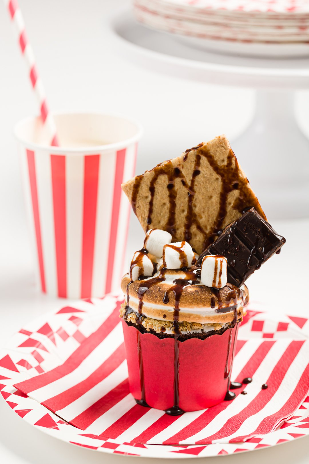 S'mores cupcake party on a red and white striped plate with a matching cup and straw in the background