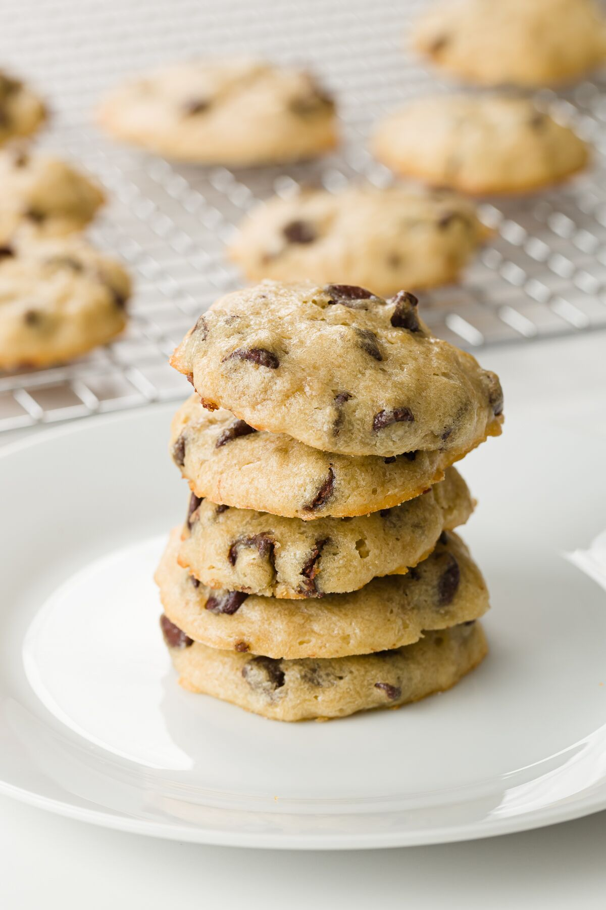Stack of cookies on a white plate with a cooling rack of cookies in the background