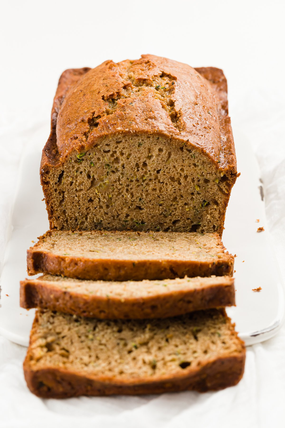 A loaf of zucchini bread with slices falling off the front of it