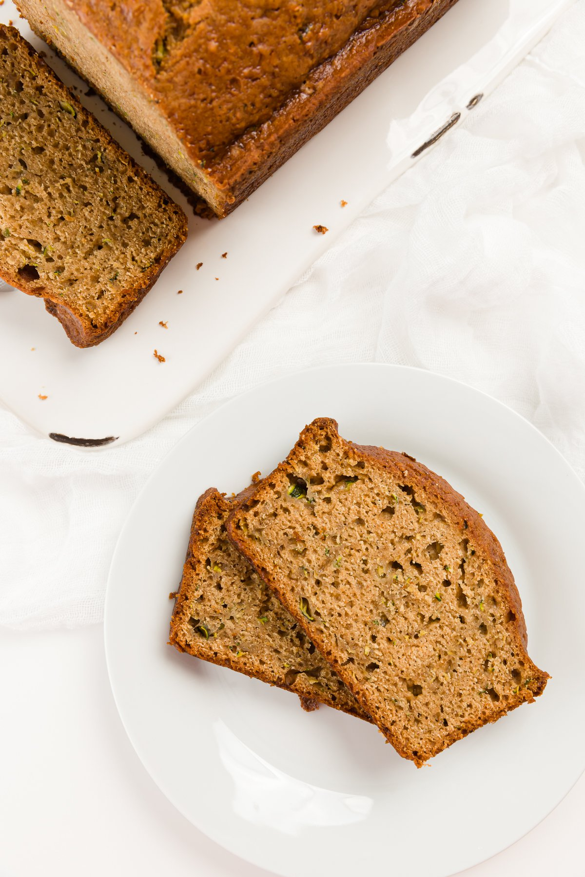 two slices of zucchini bread on a while plate with the loaf in the background