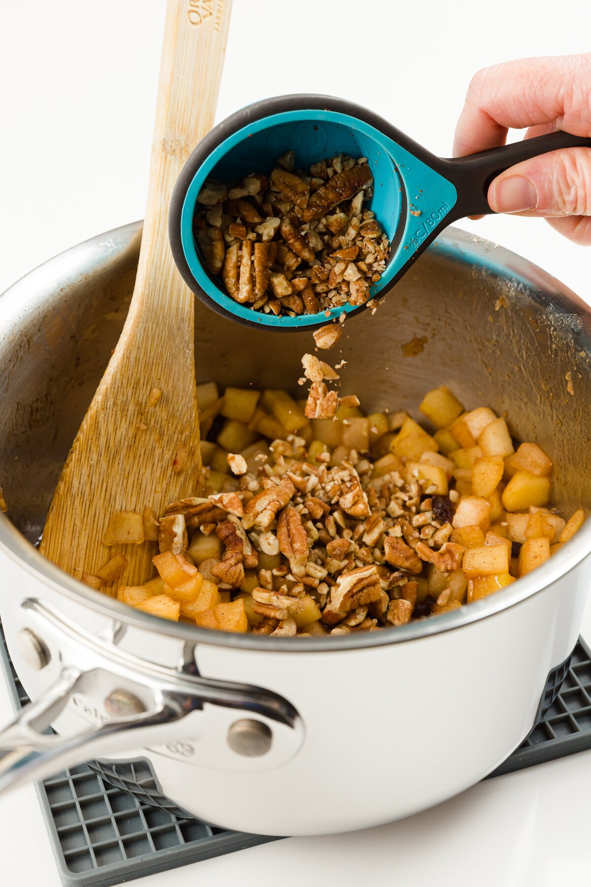 Adding nuts to pot of cooked apples
