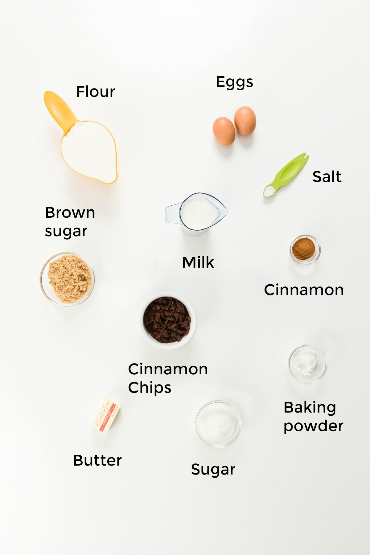 overhead photo of cinnamon muffin ingredients, labeled: flour, eggs, brown sugar, milk, salt, cinnamon, cinnamon chips, butter, sugar, and baking powder
